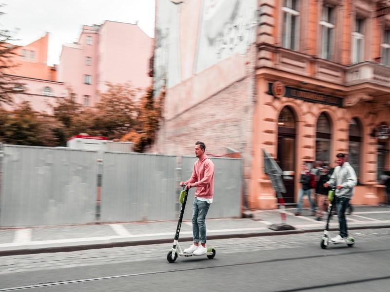 uomo in strada alla guida di un monopattino elettrico